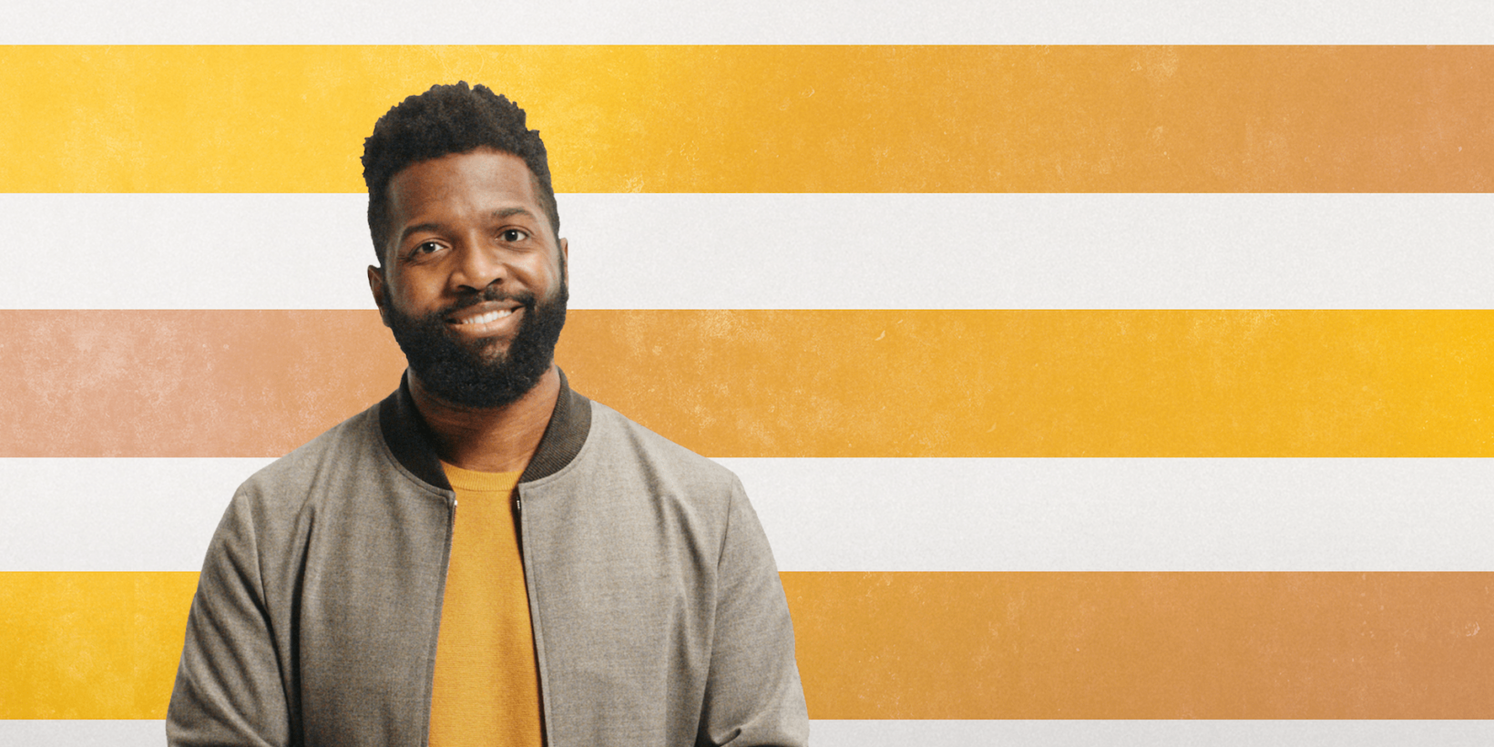 Baratunde Thurston standing in front of striped background