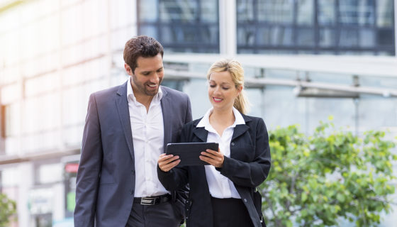 Business people walking outside looking at tablet together